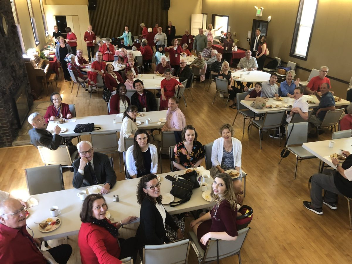 Parishioners sit at tables in the Parish Hall and smile up at the photographer